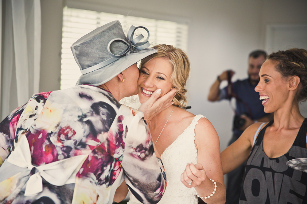 so much happiness, mother of the bride walked in and I am just smiling away while I am covering up the bride's sun burnt skin on her back