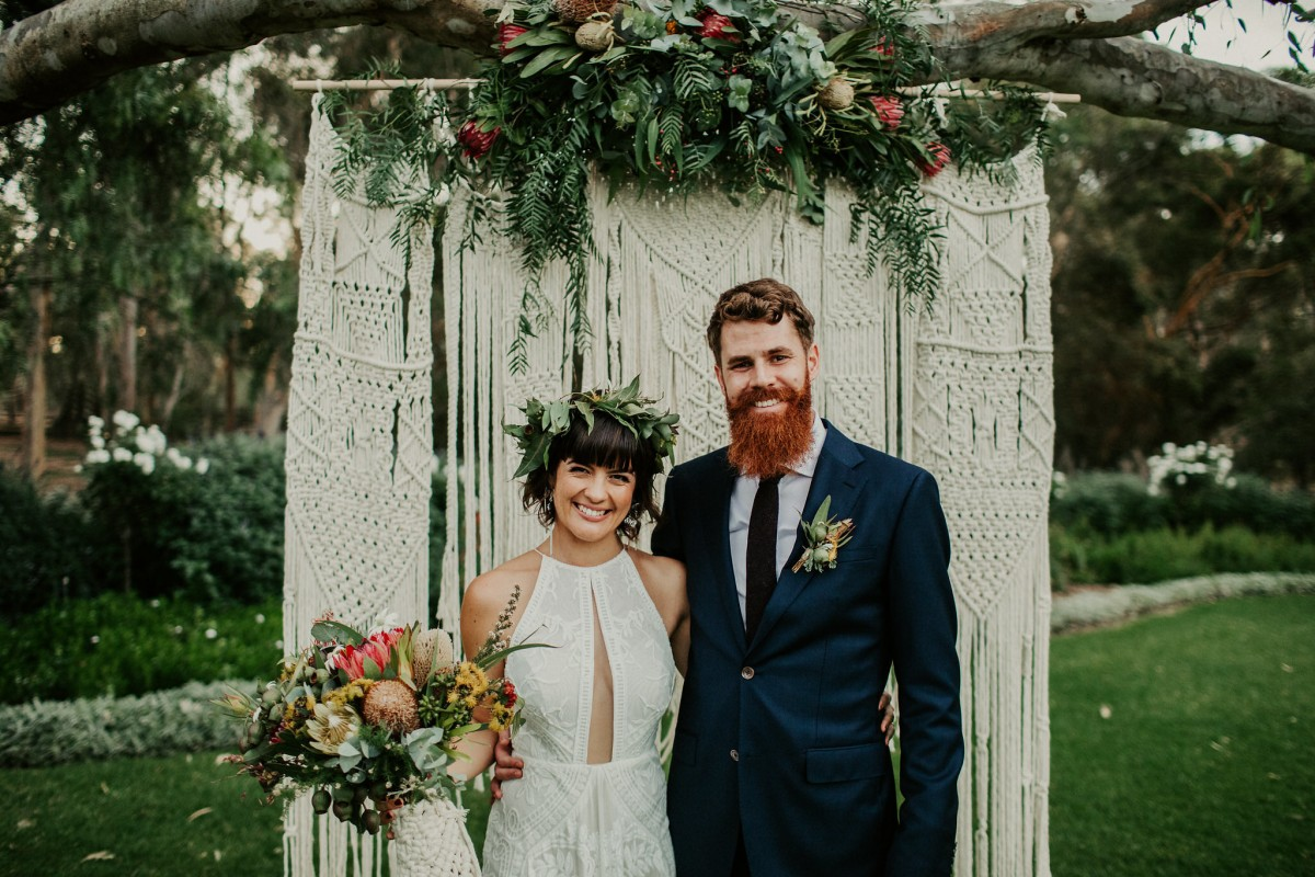 Cindy & Andrew in front of their DIY macrame backdrop